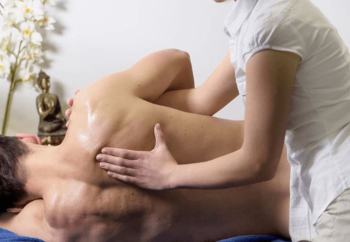 a woman doing back massage for a man