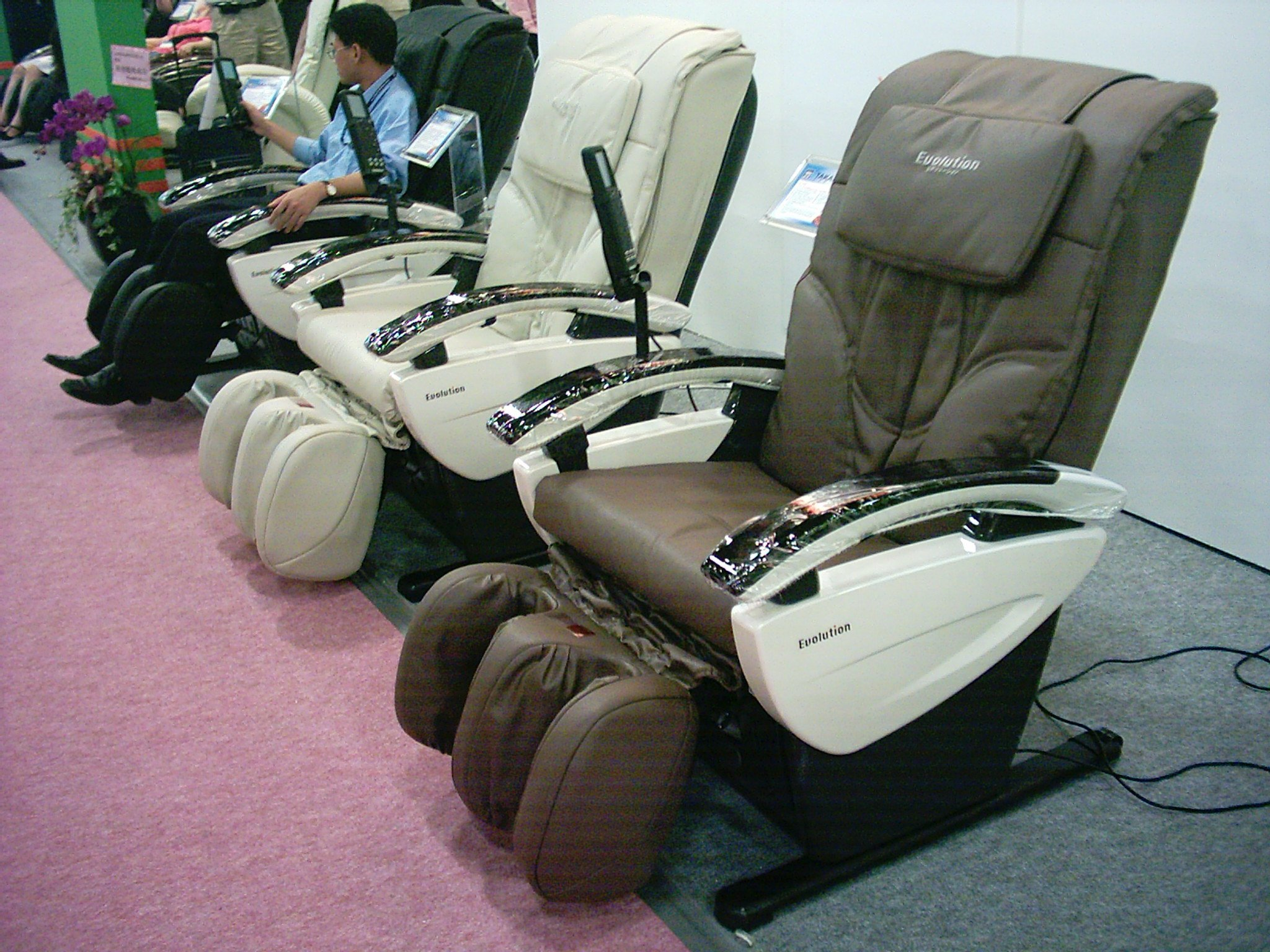 some massage chairs with the remote control siiting on the floor
