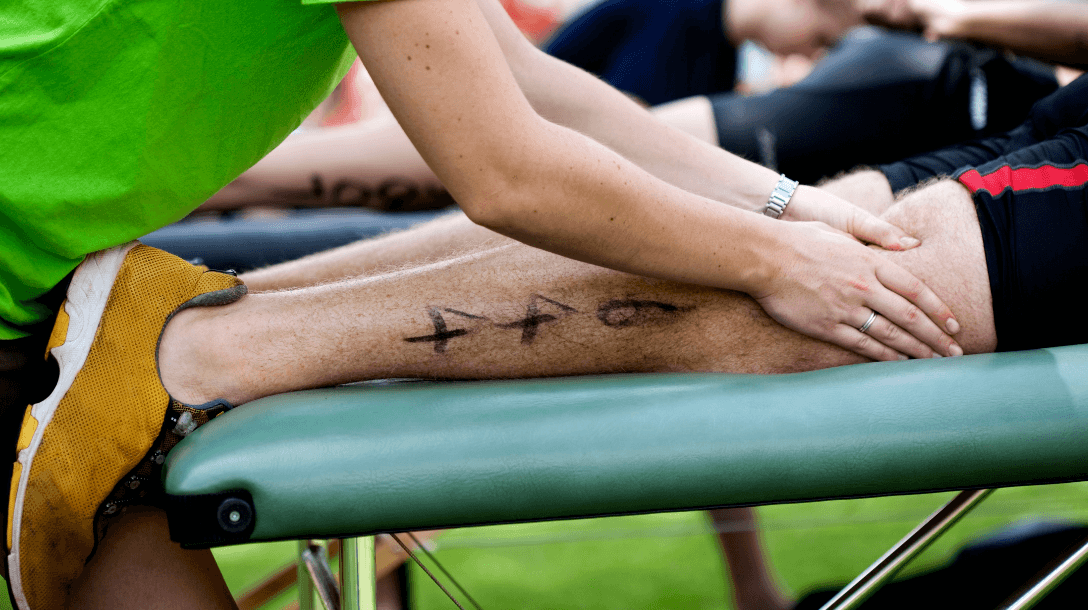 a guy is relaxing by sport massage therapist