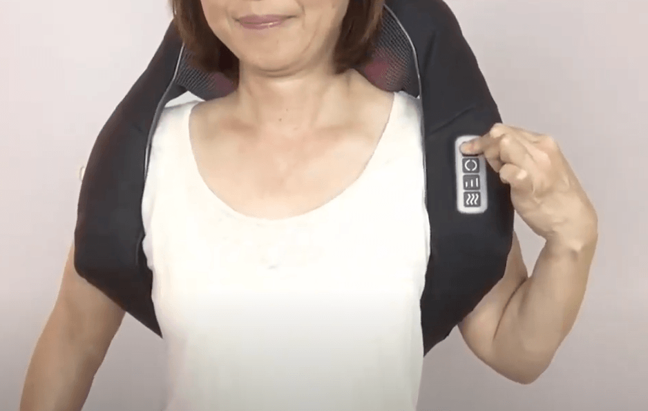 a woman pressing the massage notes on her neck and shoulder massager
