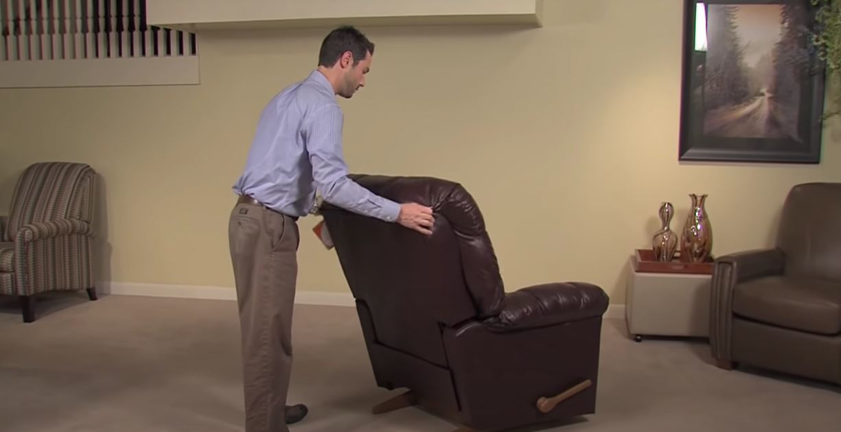 a man are moving a recliner