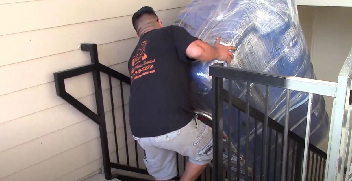 A man is moving recliner to upstair