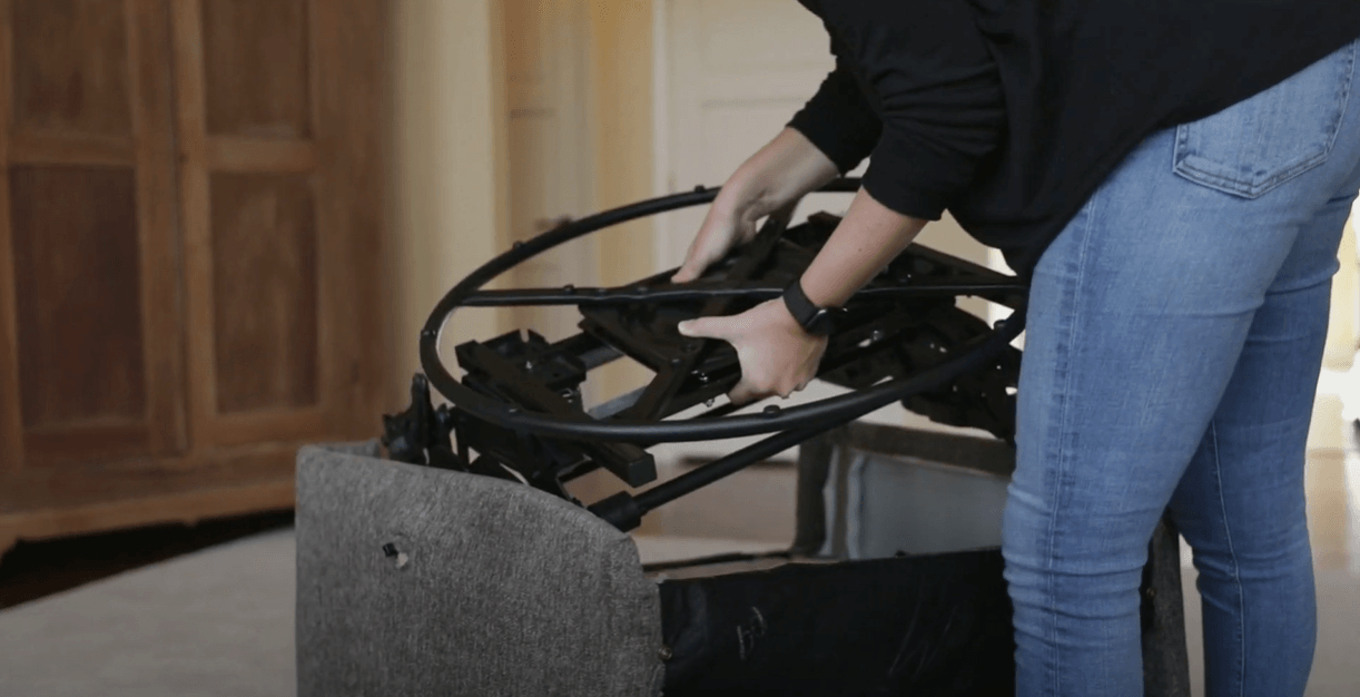 A woman is dismantling a recliner