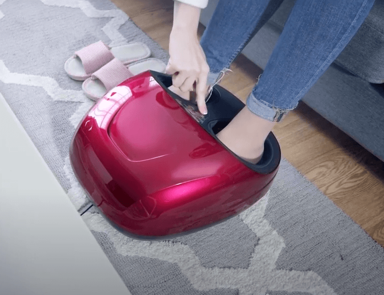 a girl pressing the button on her burgundy foot machine