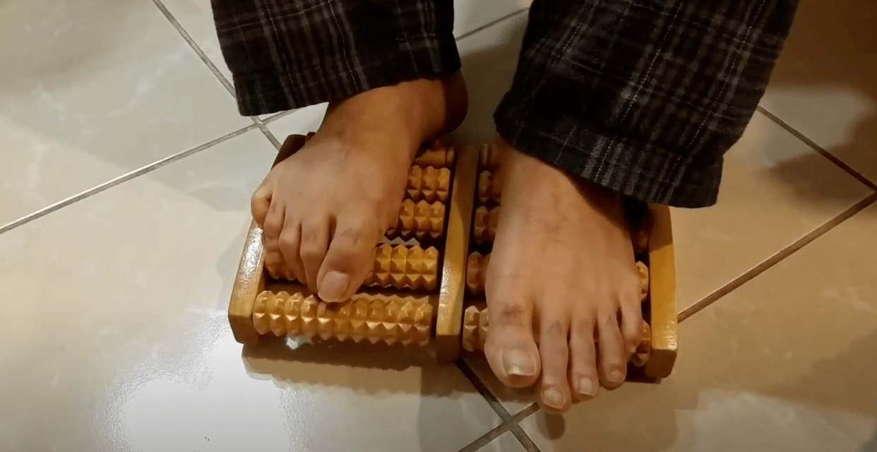 the lady using wooden foot massager