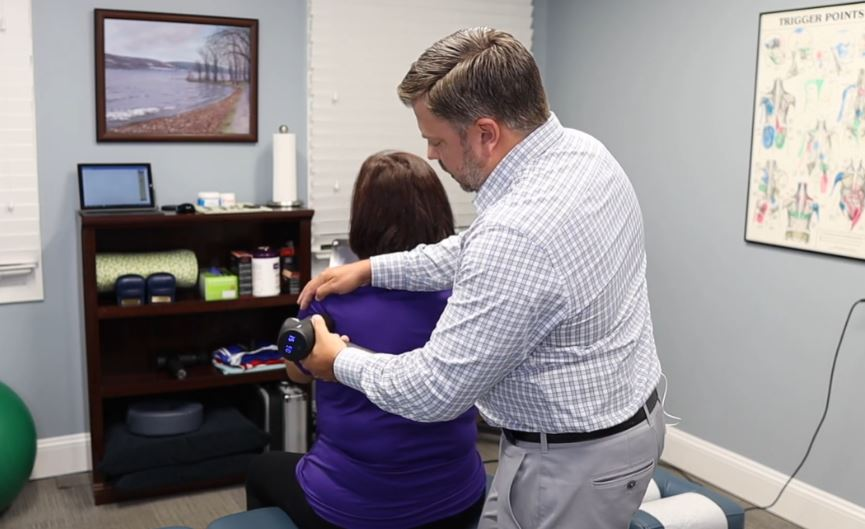 woman using massage gun